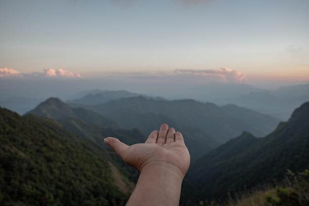 Ausgestreckte hände für tageslicht und bergblick Premium Fotos