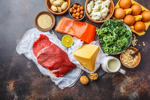 Ausgewogene ernährung lebensmittel hintergrund. proteinnahrungsmittel: fisch, fleisch, käse, quinoa, nüsse auf dunklem hintergrund. Premium Fotos