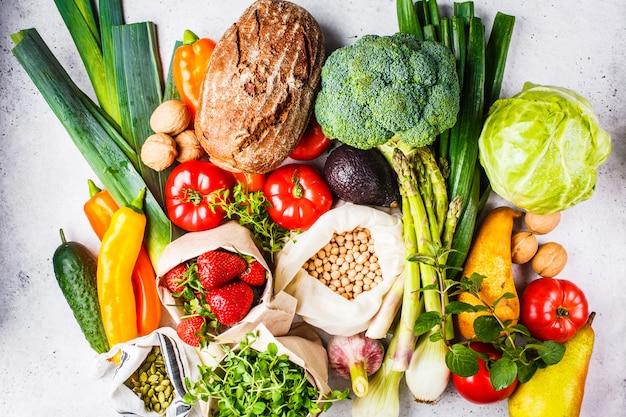 Ausgewogene vegetarische kost hintergrund gemüse, obst, beeren, nüsse, sprossen, samen, kichererbsen Premium Fotos