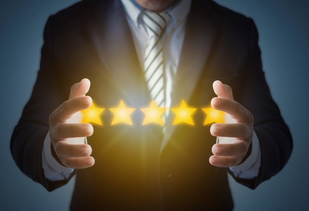 Ausgezeichneter service und beste kundenerfahrung oder guter kunde, geschäftsmann, der die bewertung mit 5 sternen auf dunkelblauem zeigt Premium Fotos