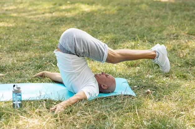 Aushaltenes ausdehnen des älteren mannes auf yogamatte Kostenlose Fotos