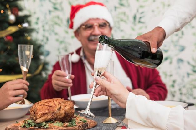 Auslaufender champagner des mannes im glas am festlichen tisch Kostenlose Fotos