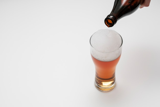 Auslaufendes bier der flasche im glas mit kopienraum Kostenlose Fotos