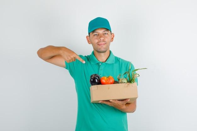 Auslieferungsmann, der finger auf gemüsebox im grünen t-shirt mit kappe zeigt Kostenlose Fotos