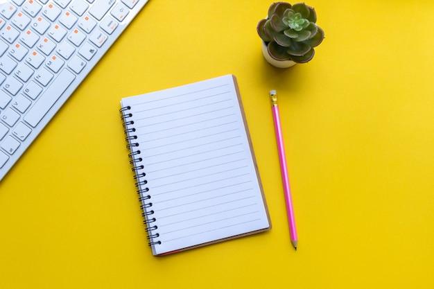 Ausrüstung und leeres notizbuch mit auf gelb Premium Fotos