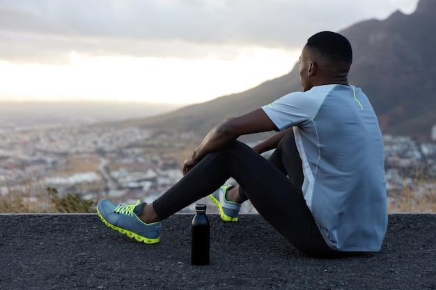 Außenansicht des entspannten afroamerikaners mit dunkler gesunder haut, trinkt wasser, sitzt auf hügel, genießt schöne landschaft, ruhige atmosphäre, berge, gekleidet in kleidung für sport. wellness Kostenlose Fotos
