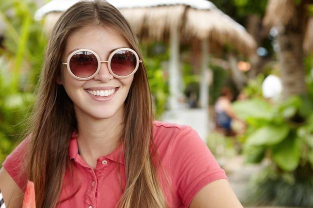 Außenaufnahme der attraktiven jungen frau in der modischen runden sonnenbrille mit spiegelgläsern, glücklich lächelnd, freizeit während der ferien genießend, gegen grüne bäume sitzend Kostenlose Fotos