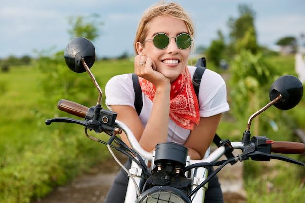 Außenaufnahme der glücklichen blonden motorradfahrerin trägt lässiges t-shirt und sonnenbrille, schaut mit fröhlichem ausdruck in die ferne, sitzt auf dem motorrad, posiert auf dem land. reisen und freiheit Kostenlose Fotos