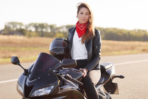 Außenaufnahme der hübschen bikerin trägt rote banadana und lederjacke Kostenlose Fotos