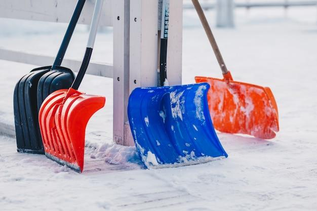 Außenaufnahme von bunten schaufeln gegen schneehintergrund während des winters Premium Fotos