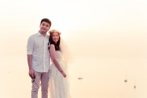Außenporträt der asiatischen braut und des bräutigams, die aufwerfen Premium Fotos