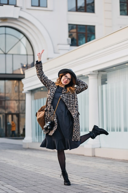 Außenporträt der eleganten jungen dame mit braunem rucksack, der mantel und hut trägt. attraktive frau mit lockigem haar, die springend spricht und spaß hat. Kostenlose Fotos