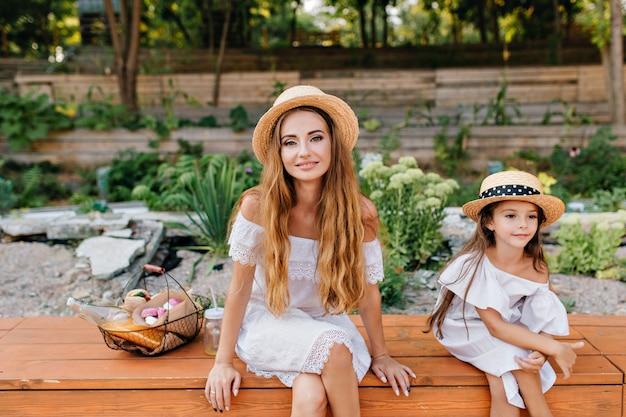 Außenporträt der erfreuten jungen frau und des mädchens, die mit gekreuzten beinen im park auf natur nach dem picknick sitzen. foto der bezaubernden dame mit korb des essens, das zeit mit tochter im garten verbringt. Kostenlose Fotos