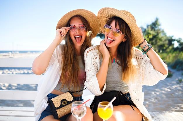 Außenporträt der firma glücklich lustige hipster-mädchen, die auf dem strandcafé verrückt werden, leckere cocktails lachen und lächeln, vintage helle boho-sommeroutfits, beziehungen und spaß trinken. Kostenlose Fotos