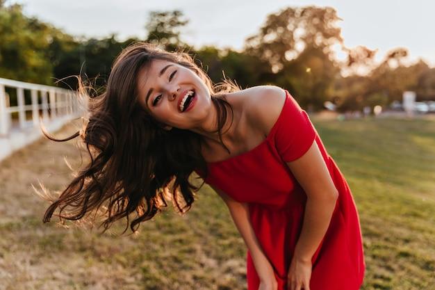 Außenporträt der gut gelaunten jungen dame im roten kleid, das glück ausdrückt. foto des erfreuten mädchens mit braunem haar, das auf natur aufwirbelt Kostenlose Fotos
