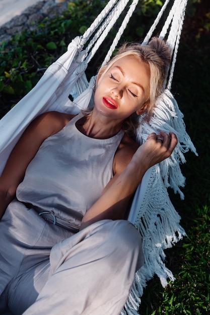 Außenporträt der kaukasischen frau im klassischen overall mit rotem lippenstift durch hängematte im urlaub außerhalb des villenhotels, meerseite Kostenlose Fotos