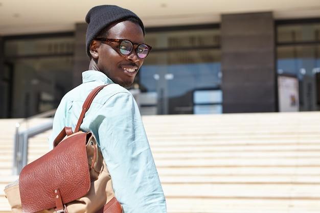 Außenporträt des fröhlichen jungen männlichen schriftstellers, der zum modernen gebäude für vorstellungsgespräch eilt Kostenlose Fotos