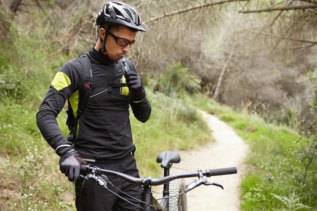 Außenporträt des hübschen professionellen fahrers in der fahrradkleidung, die lenker des schwarzen motorgetriebenen fahrrads hält, trinkwasser aus plastikrohr während der kleinen pause während des fahrens im wald Kostenlose Fotos