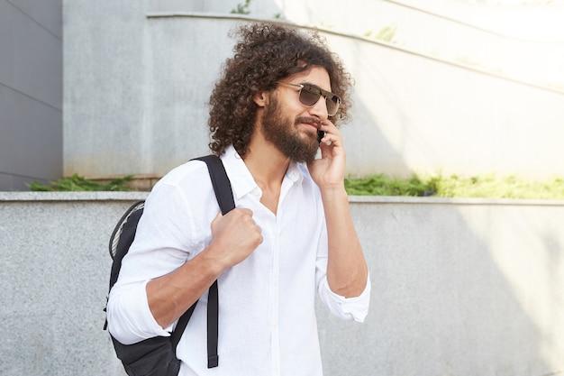 Außenporträt des jungen mannes mit lockigem haar und üppigem bart, der die straße entlang geht, während mit telefon telefonierend, weißes hemd und schwarzen rucksack tragend Kostenlose Fotos