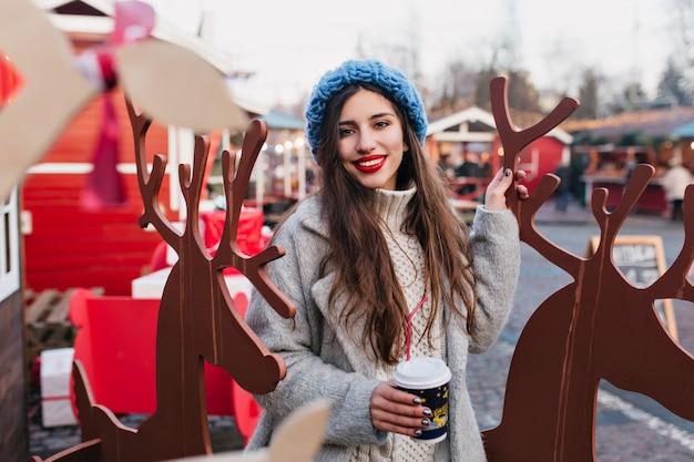 Außenporträt des langhaarigen mädchens mit der tasse kaffee, die nahe spielzeughirsche im winterurlaub aufwirft. foto der reizenden frau im blauen hut, der neben weihnachtsdekoration im park steht. Kostenlose Fotos