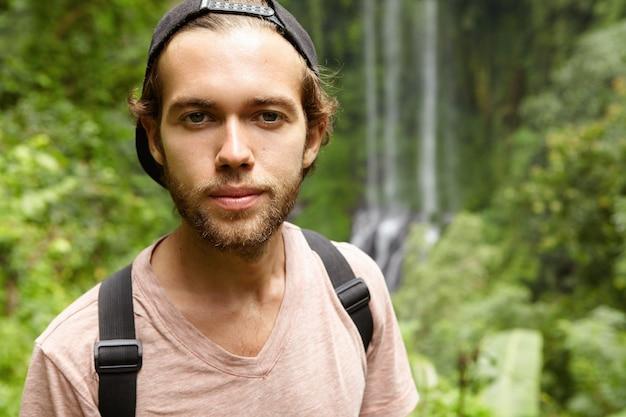 Außenporträt des modischen jungen bärtigen mannes, der schwarze hysterese rückwärts steht, die gegen exotische grüne natur mit wasserfall steht. kaukasische touristen verbringen urlaub im regenwald Kostenlose Fotos