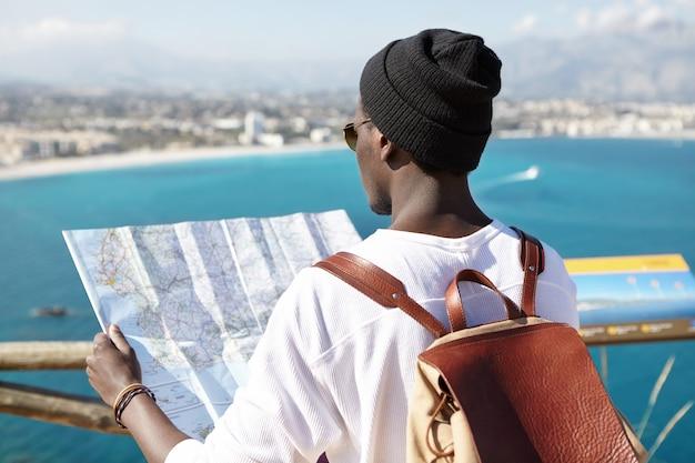 Außenrückaufnahme des dunkelhäutigen touristen mit lederrucksack auf seinen schultern, der papierführer in seinen händen hält, mit blick auf erstaunliche europäische ansicht der europäischen seeküste, die auf aussichtsplattform steht Kostenlose Fotos