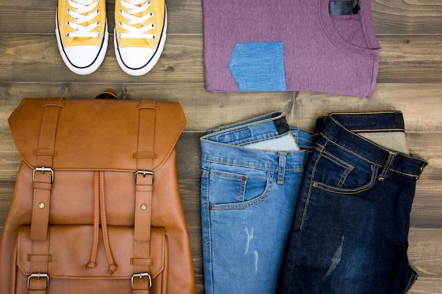 Ausstattungen des reisenden, junge, mann, zufällige ausstattungen der männer auf hölzernem bretthintergrund Premium Fotos