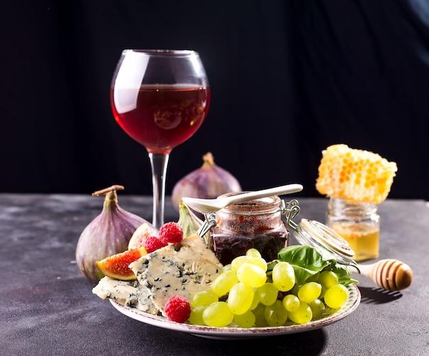 Auswahl an käse, beeren und trauben mit rotwein in gläsern. auf stein Premium Fotos