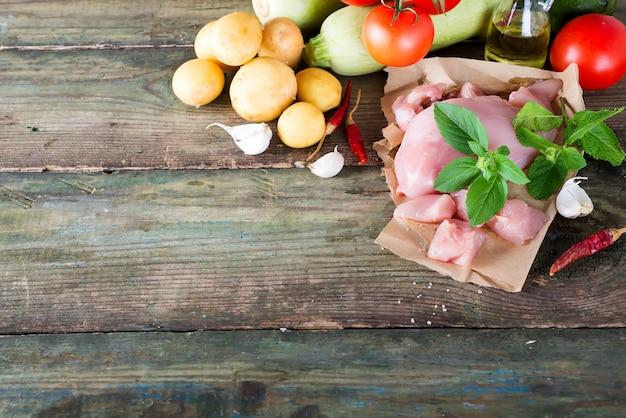 Auswahl des rohen fleisches des hühners mit gemüse am hölzernen brett. magere proteine. Premium Fotos