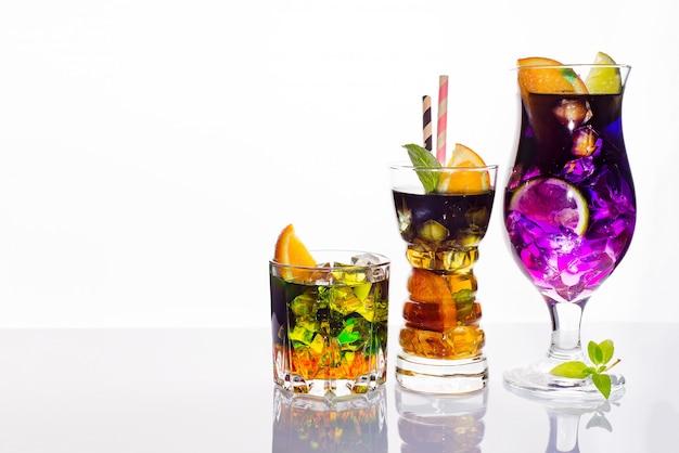 Auswahl von bunten festlichen getränken, von alkoholischen getränken und von cocktails in eleganten gläsern auf weiß Premium Fotos