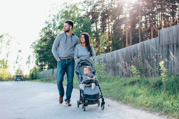 Authentische familie mit dem netten baby bo, das beim spaziergängergehen sitzt Premium Fotos