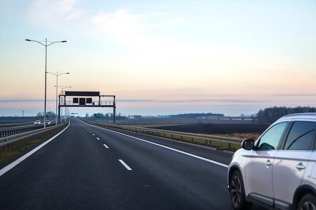 Auto auf landstraße mit leeren richtungsverkehrsschildern. Premium Fotos