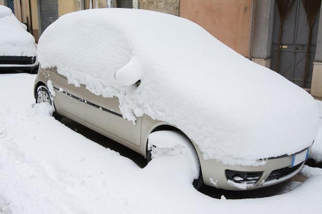 Auto bedeckt und umgeben von schneeverwehungen nach einem schneesturm Premium Fotos
