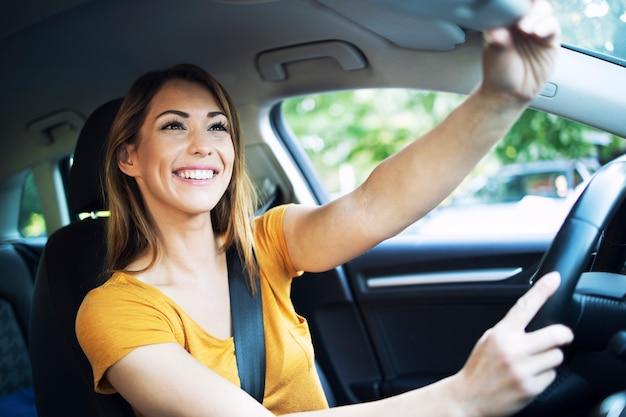 Auto-innenansicht der weiblichen fahrer, die spiegel vor dem fahren eines autos einstellen Kostenlose Fotos