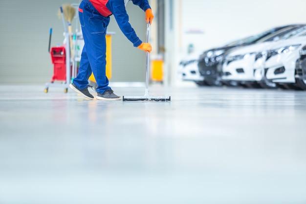 Auto-mechaniker-reparatur-service-center-reinigung mit mopps, um wasser vom epoxidboden zu rollen. in der autoreparaturwerkstatt. Premium Fotos