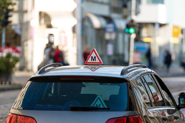 Auto mit lettischem fahrschulschild auf dach, defokussierte straße mit ampeln Premium Fotos