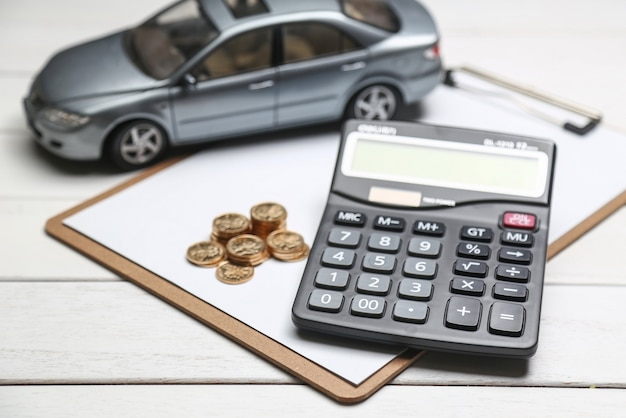 Auto-modell, taschenrechner und münzen auf weißem tisch Kostenlose Fotos