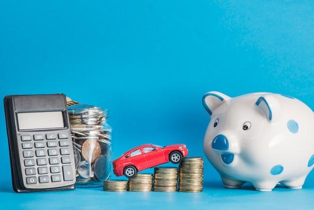 Auto über den münzenstapel mit taschenrechner; einmachglas; keramik sparschwein gegen blauen hintergrund Kostenlose Fotos