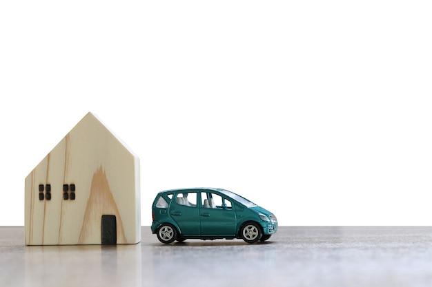 Auto und ein spielzeughaus auf dem holzboden lokalisiert auf weiß und haben beschneidungswege. Premium Fotos