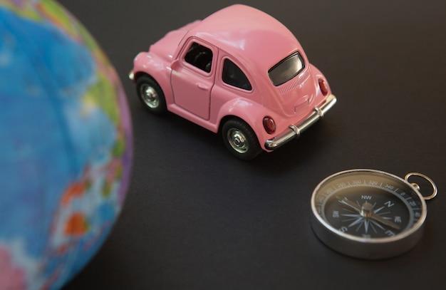 Auto und kugel mit kompaß auf schwarzem Premium Fotos