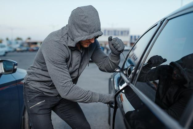 Autodieb, der türschloss bricht, krimineller job, einbrecher. männliches räuberöffnungsfahrzeug mit kapuze auf dem parkplatz. Premium Fotos