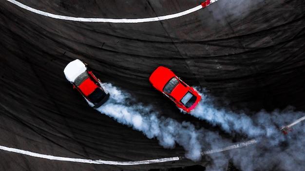 Autodriftschlacht, driftkampf mit zwei autos auf der rennstrecke mit rauch, luftbild. Premium Fotos