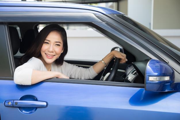 Autofahren der asiatinnen und lächeln glücklich mit frohem positivem ausdruck während der fahrt, reise zu reisen, leute genießen, transport und entspannte glückliche frau auf roadtrip-ferienkonzept zu lachen Premium Fotos