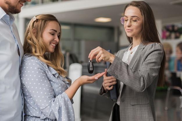 Autohändler, der einer lächelnden frau schlüssel gibt Kostenlose Fotos