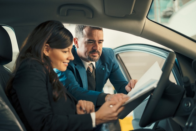 Autohändler, der geschäftsfrauvertrag im autosalon zeigt. Premium Fotos