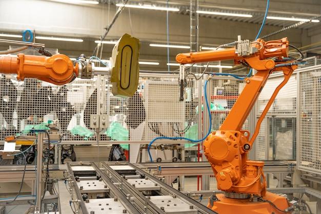 Automatischer roboterarm im werk zur präzisen herstellung und zusammenführung einzelner teile zu einem ganzen. robotisierungsproduktion. industrie 4.0 Premium Fotos