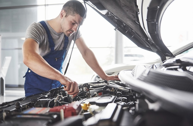 Automechaniker arbeitet in der garage. reparaturdienst. Kostenlose Fotos