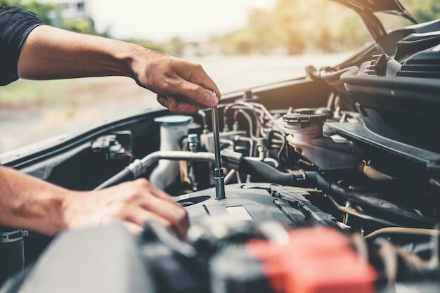Automechaniker, der in der garage arbeitet techniker hände des automechanikers, der in der autoreparatur arbeitet Premium Fotos