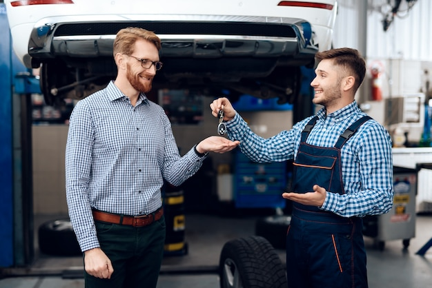 Automechaniker gibt dem erfüllten kunden autoschlüssel. Premium Fotos