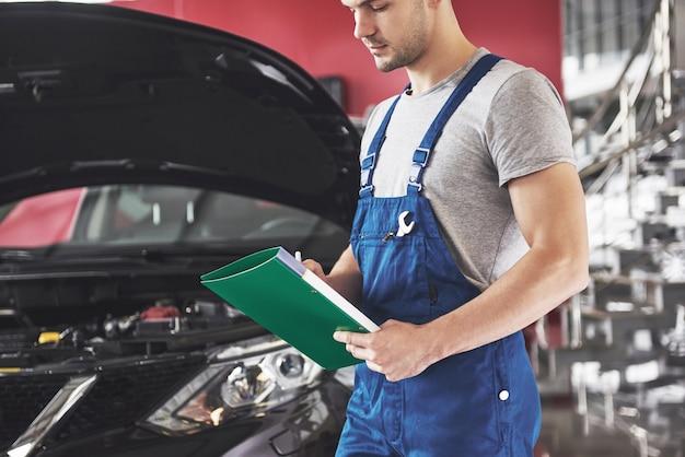 Automechaniker mann oder schmied mit zwischenablage in der werkstatt. Kostenlose Fotos
